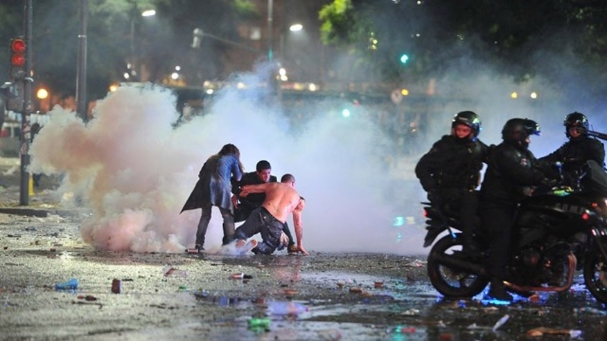 July 13, 2014: Soccer fans in Buenos Aires try to escape from a tear gas cloud and a police water cannon, used to restrain a group of youths who hurled rocks and vandalized stores, at a rally to celebrate Argentina's performance in a 1-0 loss to Germany in the World Cup final.  (AP Photo/Victor Carreira)