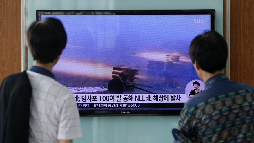 July 14, 2014 - People at Seoul Railway Station in Seoul, South Korea, watch a TV news report on North Korea firing artillery shells into waters near its sea border with South Korea, Seoul's military said, a day after the country test-launched two ballistic missiles in the latest of a series of weapon tests.