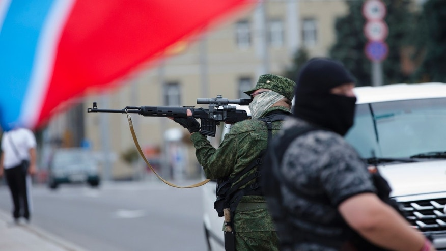 July 13, 2014 - Donetsk People's Republic fighters stand guard during a pro-Russian meeting in the city of Donetsk, eastern Ukraine.