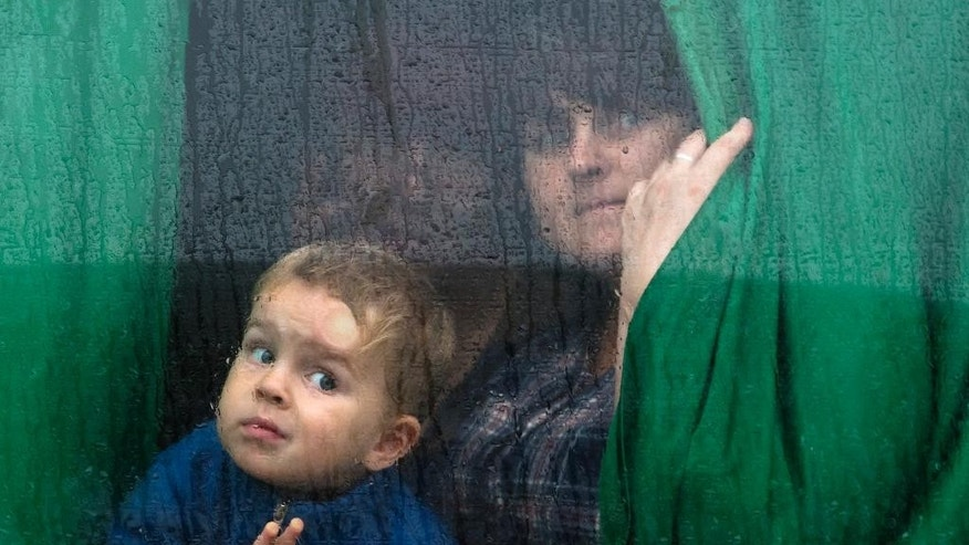People look out a bus window as they depart to seek refugees to Russia in the city of Donetsk, eastern Ukraine Monday, July 14, 2014. Five busloads of Internally Displaced People from the towns of Slavyansk, Karlovka, Maryinka and Donetsk left here Monday morning for the Rostov region in Russia to ask for refugee status there. (AP Photo/Dmitry Lovetsky)