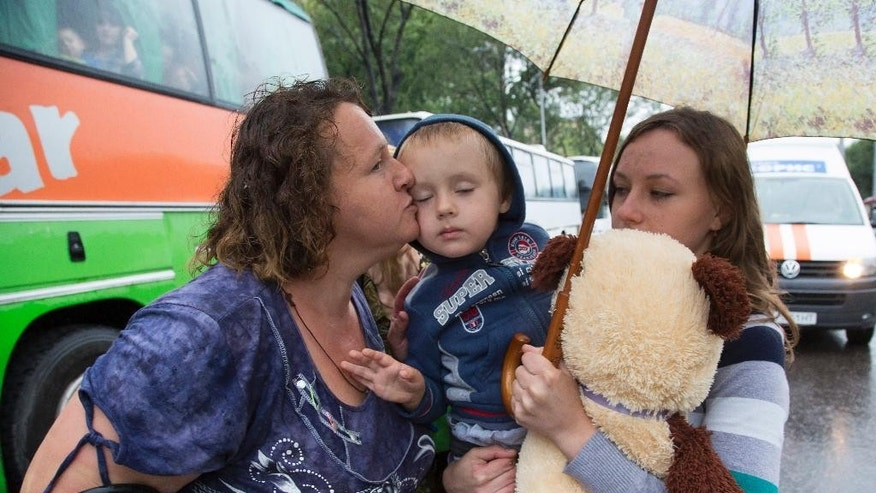 A woman, whose name is not given, kisses her grandson as they depart as refugees to Russia in the city of Donetsk, eastern Ukraine Monday, July 14, 2014. Five busloads of Internally Displaced People from the towns of Slavyansk, Karlovka, Maryinka and Donetsk left here Monday morning for the Rostov region in Russia to ask for refugee status there. (AP Photo/Dmitry Lovetsky)