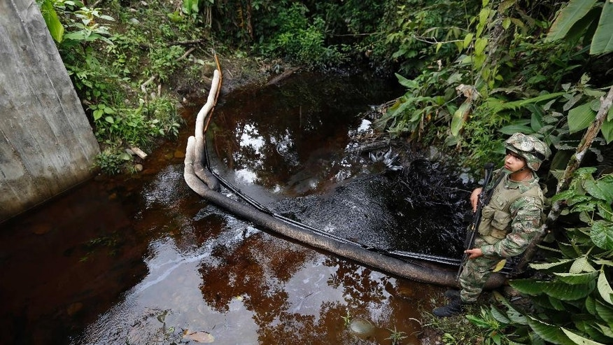 A soldier stands along a creek contaminated with crude oil in Puerto Asis, in Colombia's southwestern state of Putumayo, Tuesday, July 15, 2014. Authorities are trying to control an oil spill that, according to the Minister of Mining, Amylkar Acosta, was caused when rebels of the Revolutionary Armed Forces of Colombia, FARC, forced truck drivers to dump nearly four thousand barrels of crude when they intercepted a convoy of 19 trucks carrying oil near the border with Ecuador on July 1. (AP Photo/Fernando Vergara)