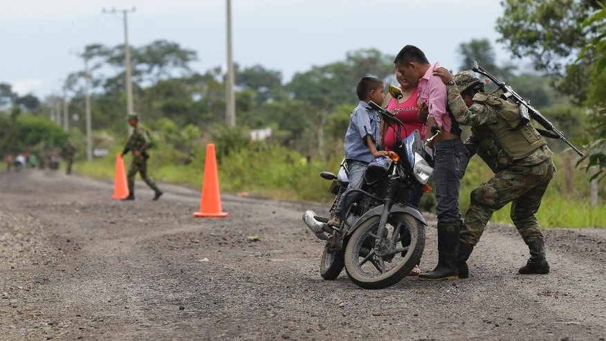 A soldier frisks a man at a military roadblock in Puerto Asis, in Colombia's southwestern state of Putumayo, Tuesday, July 15, 2014. According to the Minister of Mining, Amylkar Acosta, rebels of the Revolutionary Armed Forces of Colombia, FARC, forced truck drivers to spill nearly four thousand barrels of crude when they intercepted a convoy of 19 trucks carrying oil near the border with Ecuador. (AP Photo/Fernando Vergara)