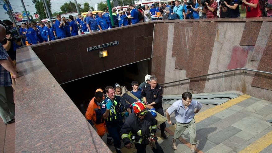 CAPTION CORRECTION REMOVES REFERENCE TO CAUSE OF DERAILMENT. THE CAUSE IS UNDER INVESTIGATION Paramedics and firefighters carry an injured man out of a subway station after a rush-hour subway train derailment in Moscow, Russia, Tuesday, July 15, 2014. A rush-hour subway train derailed in Moscow Tuesday, killing more than 20 people and injuring scores, emergency officials said. The cause of the derailment is being investigated. (AP Photo/Ivan Sekretarev)