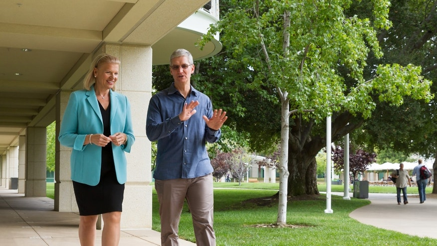 **COMMERCIAL IMAGE** In this photo distributed by Feature Photo Service for IBM: At Apple Inc's headquarters in Cupertino, California on Tuesday, July 15, 2014, Apple CEO Tim Cook and IBM CEO Ginni Rometty announced a global strategic partnership to redefine the way work gets done by transforming the way businesses and employees use mobile technology through a new class of business apps that bring IBM's big data and analytics capabilities to iPhone and iPad. The new mobile business apps for iOS are targeted for specific business opportunities in industries including retail, healthcare, banking, travel and transportation, telecommunications and insurance. (Paul Sakuma/Feature Photo Service for IBM)
