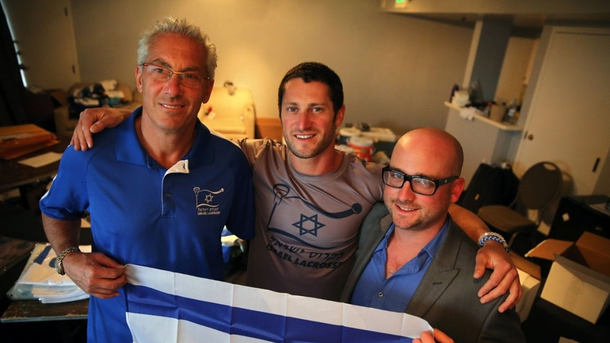 July 15, 2014: In this Israel Lacrosse head coach Bill Beroza, left, attackman Noach Milller, center, and team executive director Scott Neiss hold an Israeli flag inside a hotel room used to organize team gear, in Commerce City, Colo.