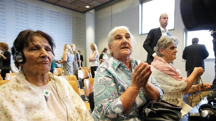 "Women from the Bosnian town of Srebrenica wait for judges to enter a civil court in The Hague, Netherlands, Wednesday, July 16, 2014. A Dutch court has declared the country liable in the deaths of more than 300 Bosnian Muslim men murdered by Bosnian Serb forces in the United Nations-declared Srebrenica ""safe haven"" 19 years ago and ordered the government to pay compensation to their widows and families. The decision was only a partial victory for families of some 8,000 men slain in the July 1995 Srebrenica massacre. In an emotionally charged hearing judges said that Dutch UN peacekeepers should have known that more than 300 men deported from the Dutch compound by Bosnian Serb forces on July 13, 1995, would be murdered. (AP Photo/Phil Nijhuis)"