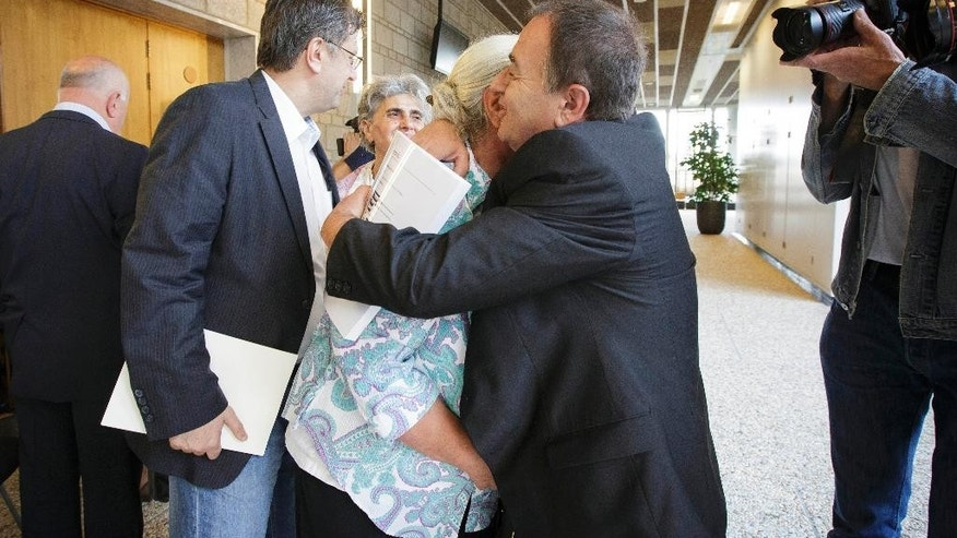 "A woman from the Bosnian town of Srebrenica is embraced by her lawyer at a civil court in The Hague, Netherlands, Wednesday, July 16, 2014. A Dutch court has declared the country liable in the deaths of more than 300 Bosnian Muslim men murdered by Bosnian Serb forces in the United Nations-declared Srebrenica ""safe haven"" 19 years ago and ordered the government to pay compensation to their widows and families. The decision was only a partial victory for families of some 8,000 men slain in the July 1995 Srebrenica massacre. In an emotionally charged hearing judges said that Dutch UN peacekeepers should have known that more than 300 men deported from the Dutch compound by Bosnian Serb forces on July 13, 1995, would be murdered. (AP Photo/Phil Nijhuis)"