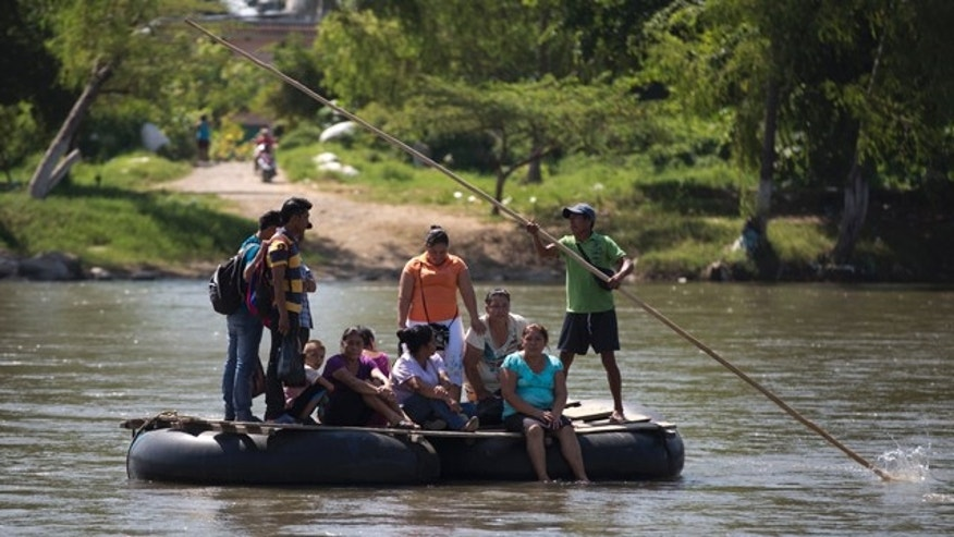 July 11, 2014: People are rafted to the Mexican shore, across the Suchiate river that separates Tecun Uman, Guatemala and Ciudad Hidalgo, Mexico, on a makeshift raft made from inner tubes of trucks attached to wooden boards. Scores of Central Americans pay a modest fee crossing the river on these improvised rafts. (AP Photo/Eduardo Verdugo)