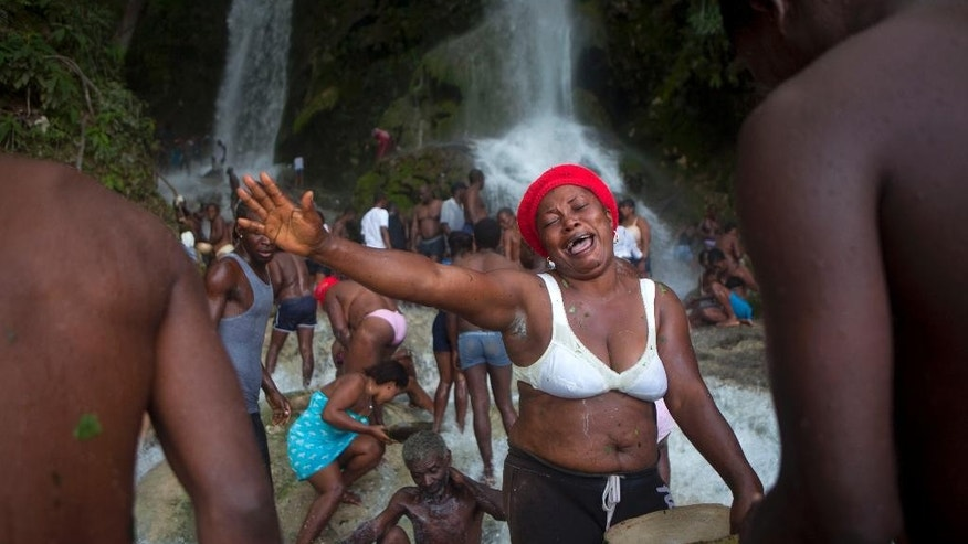 A woman sings as other Voodoo pilgrims bathe in a waterfall believed to have purifying powers during the annual celebration in Saut d' Eau, Haiti, Wednesday, July 16, 2014. An annual pilgrimage is made in honor of Haiti's most celebrated patron saint, Our Lady of Mount Carmel, who is supposed to have appeared on a palm tree in 1847 in the Palm Grove in Saut d'Eau and was integrated into Haiti's voodoo culture as the goddess of love. (AP Photo/Dieu Nalio Chery)