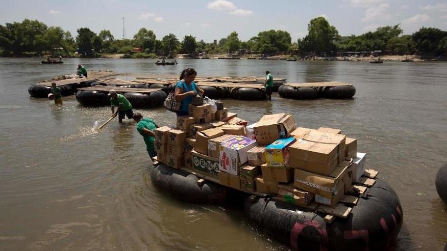In this Friday, July 11, 2014 photo, a makeshift raft made ??from inner tubes of trucks attached to wooden boards makes for the Guatemlan shore, loaded with boxes of supplies, as it crosses the Suchiate river that separates, Ciudad Hidalgo, Mexico, and Tecun Uman, Guatemala. These informal crossing has been tolerated for so long that it has become a mainstay of the southern border economy; Guatemalans resell Mexican goods on the other side, and innumerable bars and dance halls operate on the Mexican side with young Central American women working as dancers and bar maids. (AP Photo/Eduardo Verdugo)