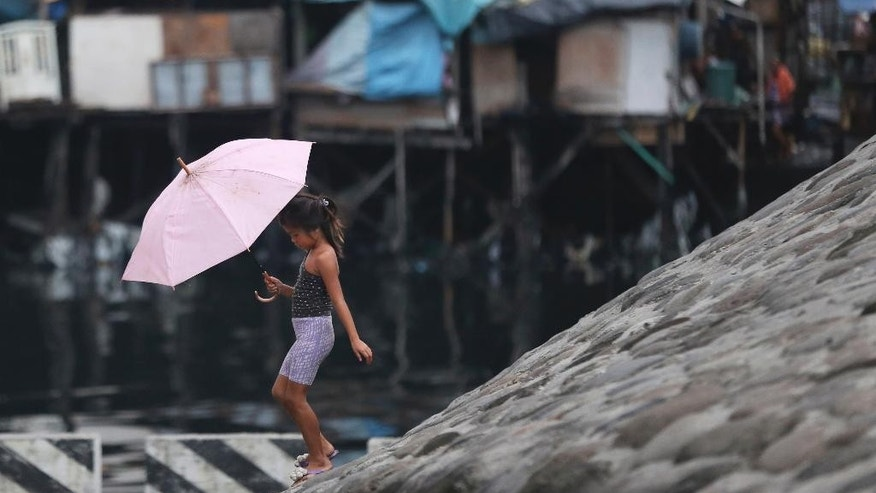A Filipino girl walks with an umbrella as they prepare for incoming Typhoon Rammasun beside Manila's bay, Philippines on Tuesday, July 15, 2014. Haunted by the memories of Typhoon Haiyan's deadly fury last year, tens of thousands of villagers fled from disaster-prone areas Tuesday as Typhoon Rammasun blew closer toward the northeastern Philippines, where it was expected to hit land at nightfall then barrel its way in the dark across densely-populated regions toward the capital, Manila. (AP Photo/Aaron Favila)
