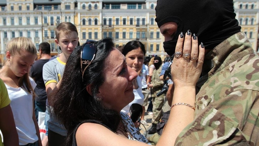 "A woman speaks with a volunteer before they were sent to the eastern part of Ukraine to join the ranks of special battalion ""Azov"", during a ceremony to take the oath of allegiance to Ukraine, in  Kiev, Ukraine Wednesday, July 16, 2014. (AP Photo/Sergei Chuzavkov)"