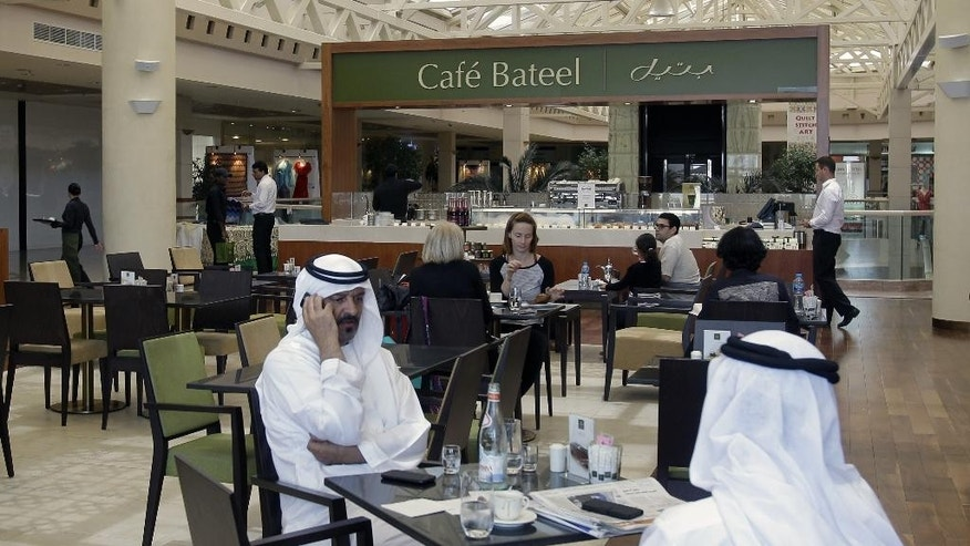 In this Wednesday, May 21, 2014 photo, Emirati and other customers enjoy their free time at the Bateel Cafe in Dubai, United Arab Emirates. Mideast entrepreneurs who have taken on international competition are now turning the tables, exporting local foods including falafel and premium dates overseas and proving that the globalization of food is not one-way. (AP Photo/Kamran Jebreili)