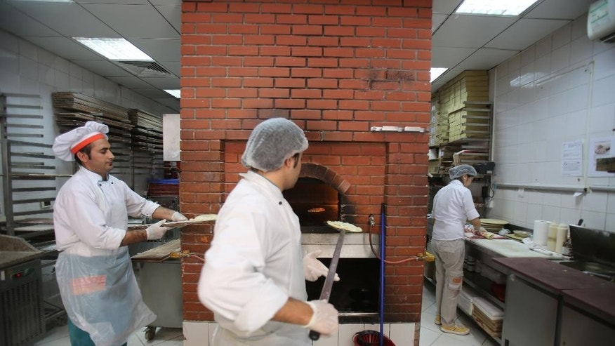 In this Monday, May 19, 2014 photo, employees work in the kitchen of a Man'oushe Street restaurant in Dubai, United Arab Emirates. Mideast entrepreneurs who have taken on international competition are now turning the tables, exporting local foods including falafel and premium dates overseas and proving that the globalization of food isn't a one-way drive-thru lane. (AP Photo/Kamran Jebreili)