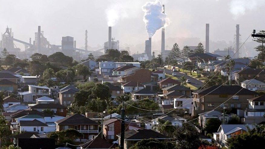 FILE - In this July 2, 2014 file photo, smoke billows out of a chimney stack of steel works factories in Port Kembla, south of Sydney. (AP Photo/Rob Griffith, File)