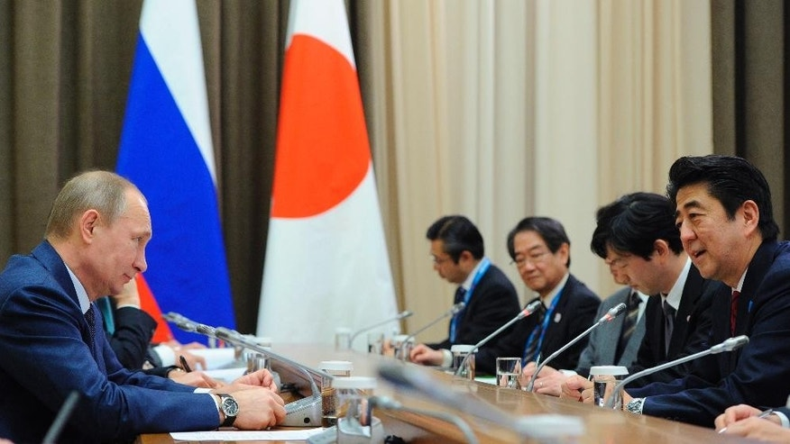 FILE - In this Feb. 8, 2014 file photo, Russian President Vladimir Putin, left, and Japanese Prime Minister Shinzo Abe meet in the Bocharov Ruchei residence in Sochi, Russia. For Japan, the ramping up of sanctions by the West against Russia can be summed up in a familiar phrase: It's complicated. The tug-of-war over Ukraine threatens to derail Abe's moves toward rapprochement with Russia. Relations between Japan and Russia suffered for decades due to a territorial dispute that has prevented the signing of a peace treaty after World War II. Yet Japan must toe the line on sanctions: It cannot spurn its main ally the U.S., nor European partners.  (AP Photo/RIA-Novosti, Mikhail Klimentyev, Presidential Press Service, File)