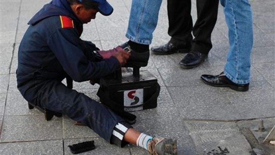In this July 7, 2014, photo, Lucas, 13, polishes shoes on a street in La Paz, Bolivia. While most of the rest of the world is trying to diminish child labor, Bolivia is on the verge of becoming the first nation legalize it from age 10. Congress has approved the proposal and all thats now required is President Evo Morales signature. (AP Photo/Juan Karita)