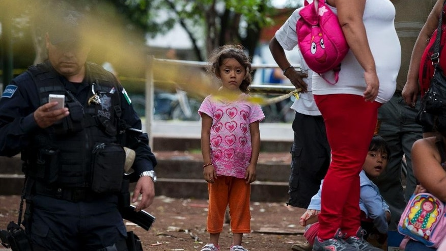A girl standing amongst relatives waiting to be reunited with their children, stands just inside a police cordon outside The Great Family group home, in Zamora, Michoacan State, Mexico, Wednesday, July 16, 2014. Mexican prosecutors said Wednesday that victims told harrowing tales of sexual abuse, beatings, hunger and filth, in a once well-regarded group home where authorities freed hundreds of adults and children in a raid. (AP Photo/Rebecca Blackwell)