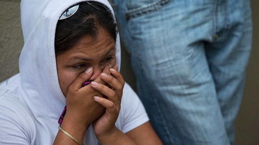 A woman sits with relatives waiting to be reunited with their children, outside The Great Family group home in Zamora, Michoacan State, Mexico, Wednesday, July 16, 2014. Mexican prosecutors said Wednesday that victims told harrowing tales of sexual abuse, beatings, hunger and filth, in a once well-regarded group home where authorities freed hundreds of adults and children in a raid. (AP Photo/Rebecca Blackwell)