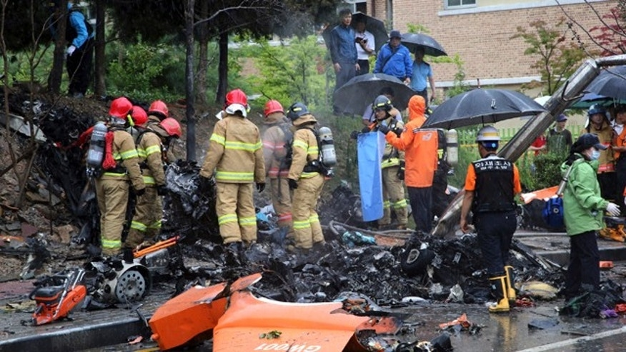 July 17, 2014: Firefighters inspect the wreckage of a helicopter which crashed near an apartment complex and school in Gwangju, South Korea. (AP Photo/Yonhap, Park Chul-hong)