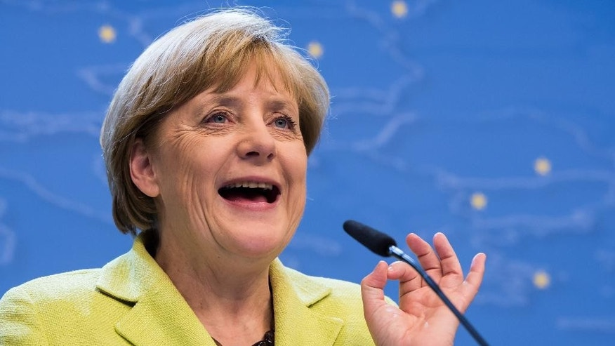 German Chancellor Angela Merkel addresses the media at the end of an EU summit at the European Council building in Brussels, early Thursday, July 17, 2014. European Union leaders ordered tougher sanctions against Russia early Thursday because of its actions in Ukraine, asking the European Investment Bank to sign no new financing agreements with Moscow. The leaders, meeting in Brussels, also agreed to act together to suspend financing of the new European Bank for Reconstruction and Development operations in Russia. (AP Photo/Geert Vanden Wijngaert)