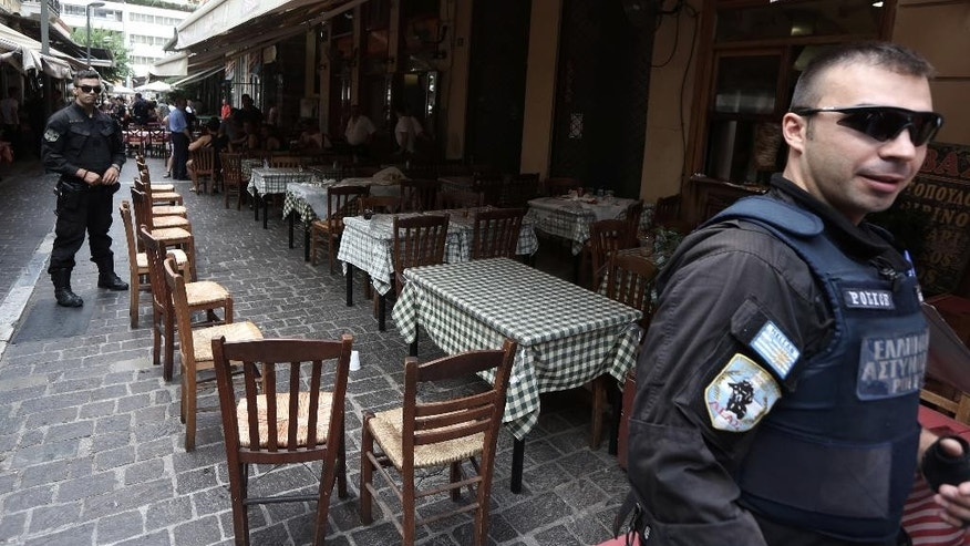 Policemen guard the scene where an Australian tourist was wounded after a shootout in the tourist area of Monastiraki in central Athens on Wednesday, July 16, 2014. Greek police arrested one of the country's most wanted men — a fugitive convicted of terrorism — during a shootout Wednesday in Athens' central tourist district that left four people wounded, authorities said. Maziotis who has been on the run along with his wife Panagiota Roupa since 2012 following their release from jail after serving the maximum 18 months in pre-trial detention. (AP Photo/Thanassis Stavrakis)