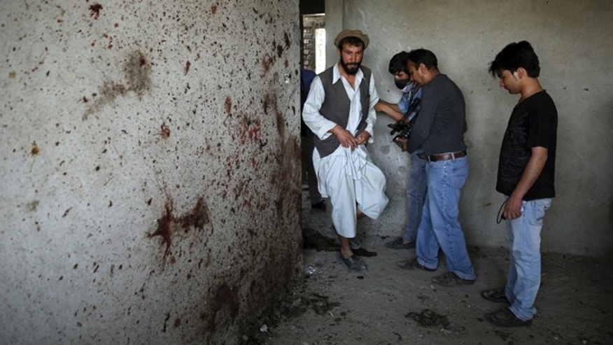 July 17, 2014: An Afghan man, left, enters a room which Taliban fighters used during a clash with Afghanistan's forces in Kabul. Gunmen launched a pre-dawn attack on the Kabul International Airport in the Afghan capital on Thursday, raining down rockets on the sprawling facility, setting off a gun battle with security forces and forcing the airport to close, officials said. (AP Photo/Massoud Hossaini)