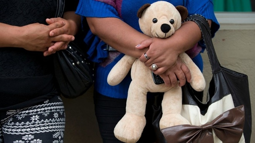 Maria Isabel Blancas Gonzalez holds her 16-year-old daughter's teddy bear, as she waits to be reunited with her, outside The Great Family group home, in Zamora, Michoacan State, Mexico, Wednesday, July 16, 2014. Blancas said she had only been permitted to see her daughter once every four months, and that her daughter told her she had been hit and had signs of physical abuse. Mexican prosecutors said Wednesday that victims told harrowing tales of sexual abuse, beatings, hunger and filth, in a once well-regarded group home where authorities freed hundreds of adults and children in a raid. (AP Photo/Rebecca Blackwell)