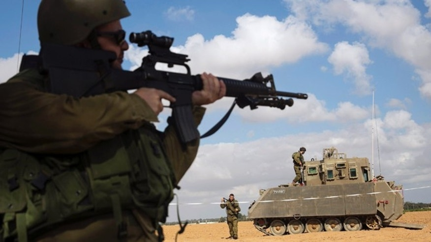 July 17, 2014: An Israeli soldier looks through the scope of his weapon outside the southern Gaza Strip.