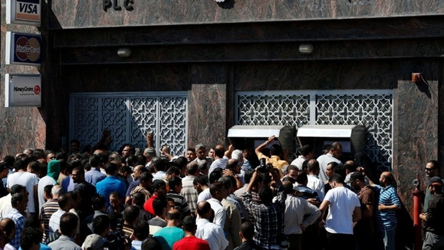 July 17, 2014: Palestinians gather to withdraw money from ATM machines in Gaza City. The Bank of Palestine opened one of its branches in Gaza City's Rimal neighborhood as the cease-fire began, drawing hundreds of people trying to withdraw money. (AP Photo/Lefteris Pitarakis)