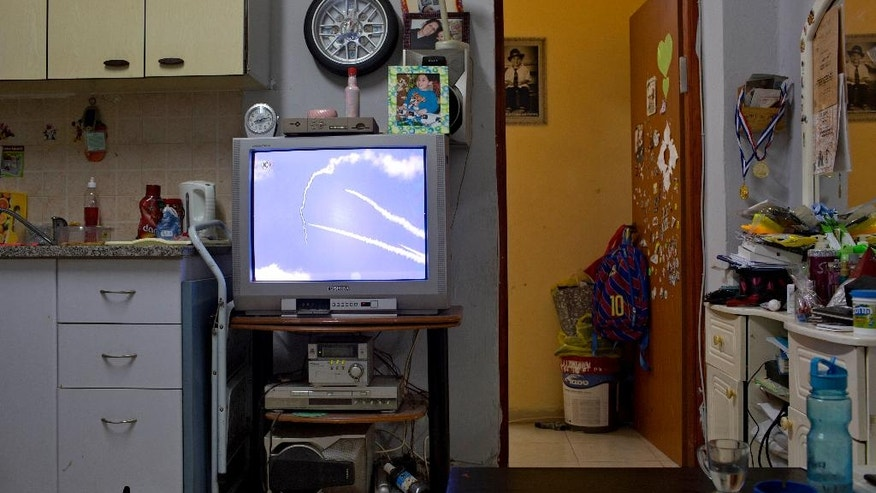 In this Tuesday, July 15, 2014 photo, a TV screen shows the ongoing fighting between Israel and Gaza at a house in south Tel Aviv, Israel. Israelis are struggling to decide whether to carry on with their routines or take emergency precautions. (AP Photo/Oded Balilty)