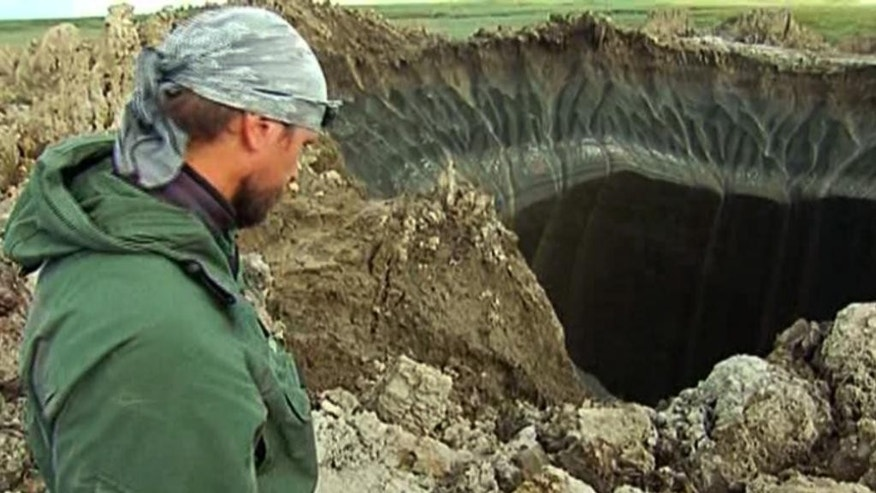 In this frame grab made Wednesday, July 16, 2014, Andrei Plekhanov, a senior researcher at the Scientific Research Center of the Arctic, stands at a crater, discovered recently in the Yamal Peninsula, in Yamalo-Nenets Autonomous Okrug, Russia. Russian scientists said Thursday july 17, 2014 that they believe a 60-meter wide crater, discovered recently in far northern Siberia, could be the result of changing temperatures in the region. Andrei Plekhanov said 80 percent of the crater appeared to be made up of ice and that there were no traces of an explosion, eliminating the possibility that a meteorite had struck the region. (AP Photo/Associated Press Television)