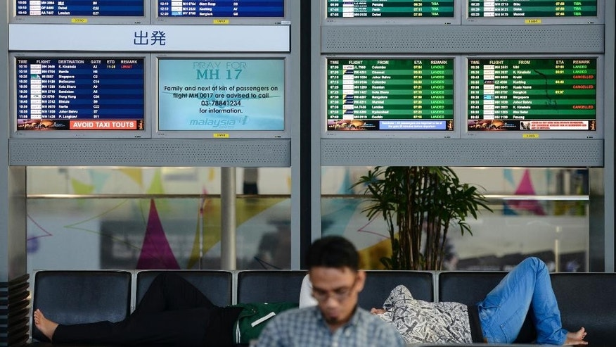 "An electronic board displaying ""Pray for MH17"" at the departure hall at Kuala Lumpur International Airport in Sepang, Malaysia, Friday, July 18, 2014. Malaysia Airlines has increased the death toll from Flight 17 that was shot down over war-torn eastern Ukraine on Thursday to 298 from 295, saying that three infants had not been included in the original list. (AP Photo/Joshua Paul)"