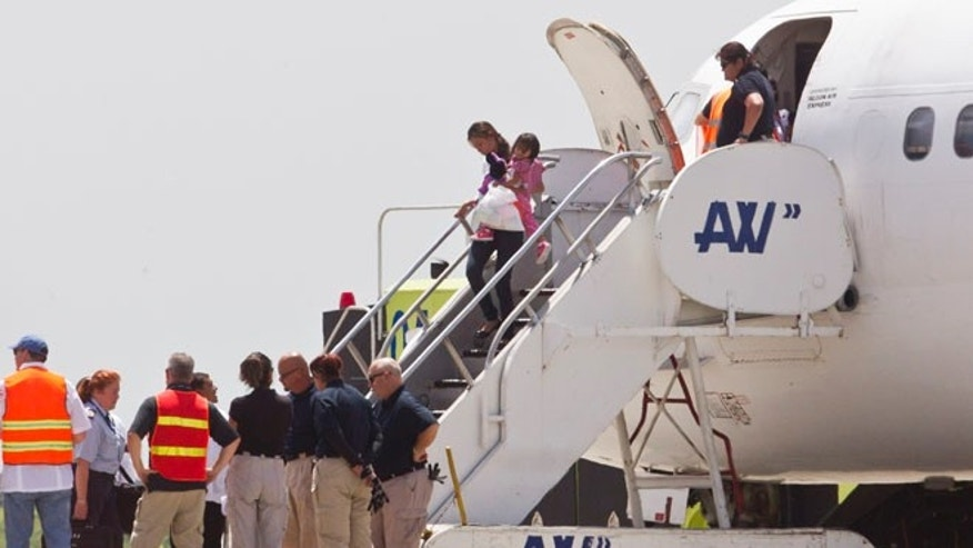 July 18, 2014: Immigration and Custom officials standby as a woman and child, who were deported from the United States, deplane at the San Pedro Sula airport, in Honduras. (AP)