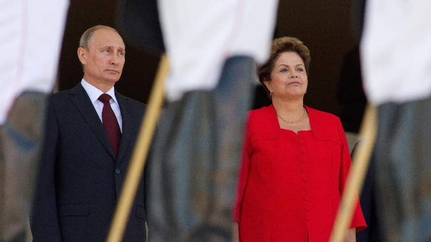 FILE - In this July 14, 2014, file photo, Russia's President Vladimir Putin, left, stands with Brazil's President Dilma Rousseff during the playing of the national anthem at Planalto presidential palace in Brasilia, Brazil. Putin said that his visit was focused on expanding commercial ties and that the timing was triggered by the summit, in Brazil of leaders from the so-called BRICS group, Brazil, Russia, India, China and South Africa. (AP Photo/Eraldo Peres, File)