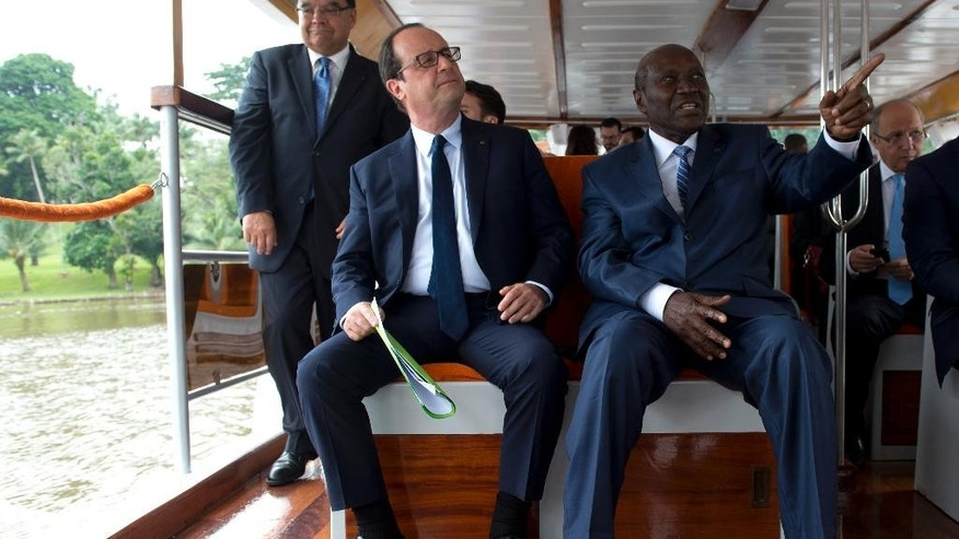 French President Francois Hollande, left, sits next to Ivorian Prime Minister Daniel Kablan Duncan, right, on a boat, Thursday, July 17, 2014 on Abidjan's lagoon, Ivory Coast, where French construction company Bouygues is building a third bridge that is presented as a key project by the Ivorian government. Hollande starts a 3-day visit to Ivory Coast, Niger and Chad. (AP Photo/Alain Jocard, Pool)