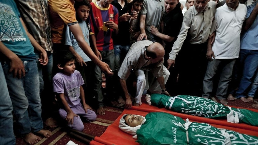 Palestinian mourners gather around the bodies of three siblings of the Abu Musallam family during their funeral in Beit Lahiya, northern Gaza Strip, Friday, July 18, 2014. Ismail Abu Musallam said three of his children: Ahmed, 11; Walaa, 14, and Mohammed, 16, were in bed when an Israeli shell slammed into the home, burying them under debris. His personal tragedy is not unique: minors make up almost one-fifth of those killed in Israel's 11-day bombardment of Hamas targets in densely populated Gaza, where half the population is under the age of 18.  (AP Photo/Lefteris Pitarakis)