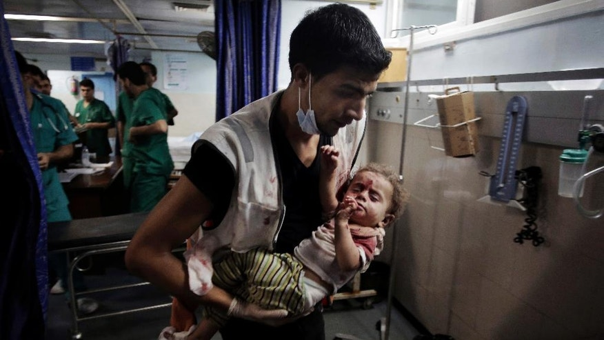 A Palestinian medic carries a wounded girl in the emergency room of Shifa hospital in Gaza City, northern Gaza Strip, early Friday, July 18, 2014. Minors make up almost one-fifth of those killed in Israel's 11-day bombardment of Hamas targets in densely populated Gaza, where half the population is under the age of 18. (AP Photo/Khalil Hamra)