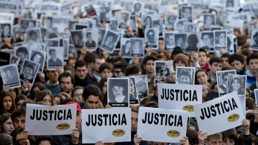 "People hold up signs that read ""Justice"" in Spanish and pictures of the victims of the 1994 bombing of the AMIA Jewish community center during a commemoration ceremony in Buenos Aires, Argentina, Friday, July 18, 2014. Friday marks the 20th anniversary of the unsolved bombing attack that left 85 dead. (AP Photo/Natacha Pisarenko)"