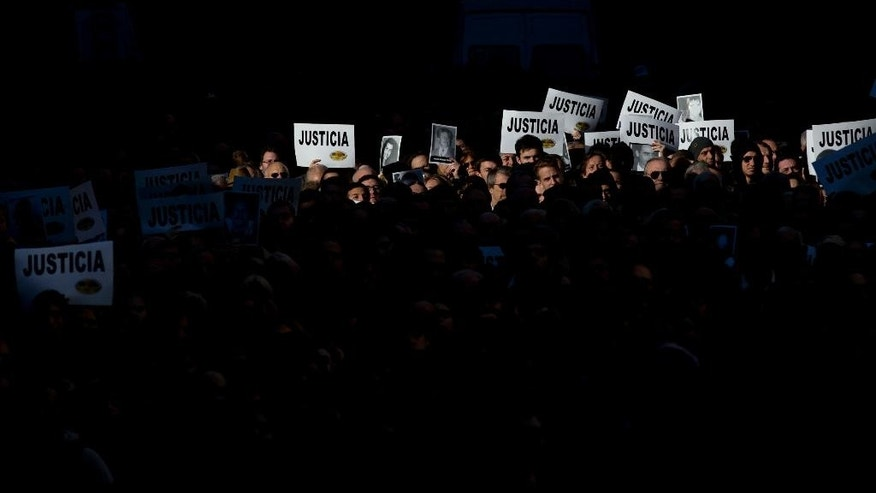 "People hold up signs that read ""Justice"" in Spanish and pictures of the victims of the 1994 bombing of the AMIA Jewish community center during a commemoration ceremony in Buenos Aires, Argentina, Friday, July 18, 2014. Friday marks the 20th anniversary of the unsolved attack that left 85 dead. (AP Photo/Natacha Pisarenko)"