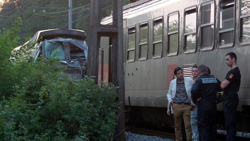 Vice prosecutor Sebastien Ellul, left, and French police officers at the scene after two trains collided in Deguin, near Pau, southwestern France, Thursday, July 17, 2014. A regional TER train and a national TGV train heading for Paris collided head on after traveling on the same track in opposite directions in the town of Deguin, 18 kilometers (11 miles) northwest of Pau and left 25 people injured. (AP Photo/Bob Edme)