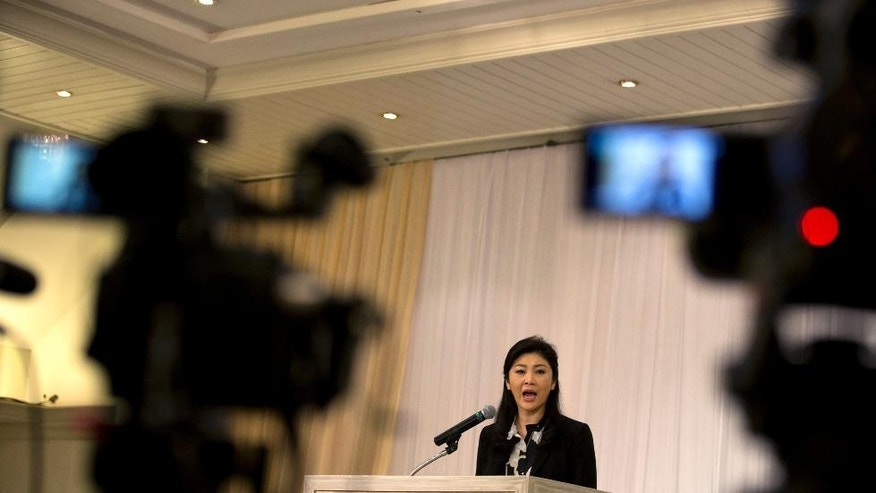 Former Prime Minister Yingluck Shinawatra talks to reporter during a press conference in Bangkok, Thailand Friday, July 18, 2014. Yingluck defended herself over the rice subsidy scheme, questioned the fairness of the investigation process and denied rumors that she will go overseas to flee the case.  An anti-corruption body has recommended criminal charges against the ousted Thai prime minister over her government's rice subsidy program, which cost the country's billions of dollars. (AP Photo/Sakchai Lalit)
