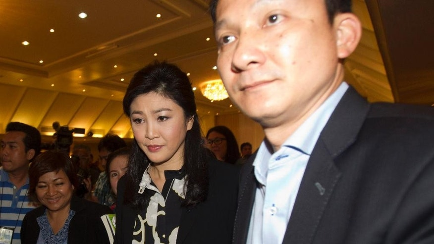 Former Prime Minister Yingluck Shinawatra leaves after a press conference in Bangkok, Thailand, Friday, July 18, 2014. Yingluck defended herself over the rice subsidy scheme, questioned the fairness of the investigation process and denied rumors that she will go overseas to flee the case. An anti-corruption body has recommended criminal charges against the ousted Thai prime minister over her government's rice subsidy program, which which cost the country's billions of dollars.(AP Photo/Sakchai Lalit)