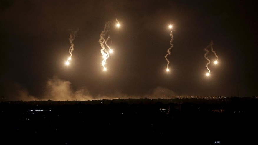 Israeli forces' flares light up the night sky in the northern Gaza Strip, early Saturday, July 19, 2014. Israeli troops pushed deeper into Gaza on Friday to destroy rocket launching sites and tunnels, firing volleys of tank shells and clashing with Palestinian fighters in a high-stakes ground offensive meant to weaken the enclave's Hamas rulers. (AP Photo/Adel Hana)