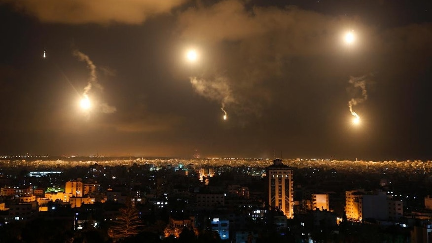 In this image made with a long exposure, the sky and the city is lit by Israeli forces' flares in the northern Gaza Strip, Friday, July 18, 2014. Israeli troops pushed deeper into Gaza on Friday to destroy rocket launching sites and tunnels, firing volleys of tank shells and clashing with Palestinian fighters in a high-stakes ground offensive meant to weaken the enclave's Hamas rulers. (AP Photo/Lefteris Pitarakis)