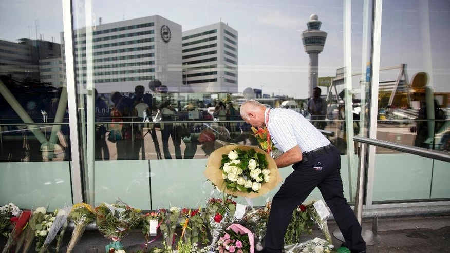 A Schiphol worker adjusts flowers people have placed outside Schiphol airport in Amsterdam, Friday, July 18, 2014. The attack on a Malaysian jetliner Thursday afternoon killed 298 people from nearly a dozen nations, more than half being Dutch, including vacationers, students and a large contingent of scientists heading to an AIDS conference in Australia. (AP Photo/Phil Nijhuis)