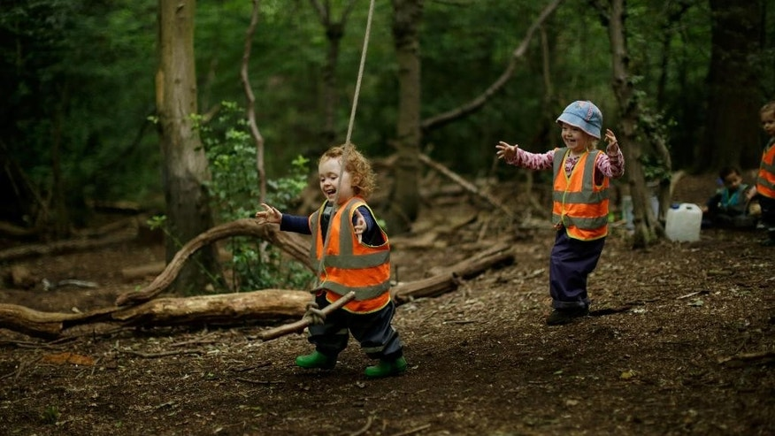 """In this photo taken Tuesday, July 8, 2014, Olive, left, and Matilda play with a rope swing at the """"Into the Woods"""" outdoor children's nursery in Queen's Wood, in the Highgate area of north London. Each morning a group of children gather at the Queens Wood camp, which the nursery team prepare each morning before the children arrive. Forest schools are increasing in popularity in the United Kingdom, with many schools offering short courses for children to spend time outdoors, building dens, climbing trees and exploring. (AP Photo/Matt Dunham)"""