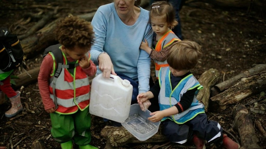 """In this photo taken Tuesday, July 8, 2014, founder Emma Shaw helps children wash their hands before eating a snack at the """"Into the Woods"""" outdoor children's nursery in Queen's Wood, in the Highgate area of north London, Tuesday, July 8, 2014. The """"Into the Woods"""" nursery was opened in April by primary school teacher Emma Shaw for children from two-and-a-half to five years in age. She said the natural environment works wonders. (AP Photo/Matt Dunham)"""