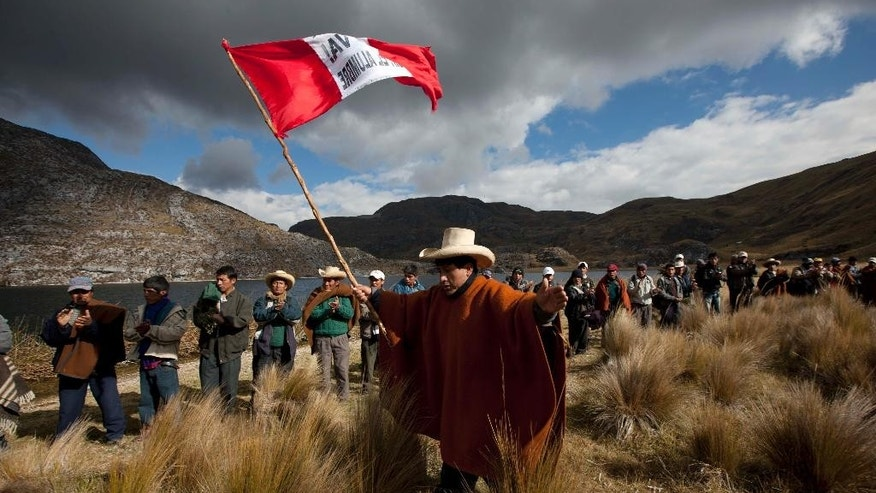 FILE - In this Aug. 21, 2012 file photo, residents march during a demonstration against the Conga gold and silver mining project in Mamacocha Lagoon, Peru. A new law enacted July 11 by President Ollanta Humala, weakens environmental protections in the Andean nation as it prepares to host international climate-control talks. Activists predict the weakened protections will spark more clashes between police who protect mines and highlanders angered by contamination and diminished water supplies they blame on the open pits. (AP Photo/Martin Mejia, File)